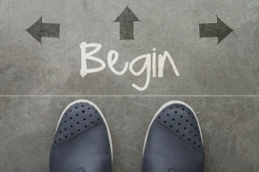 Hand drawn BEGIN design word on front of business man feet as concept